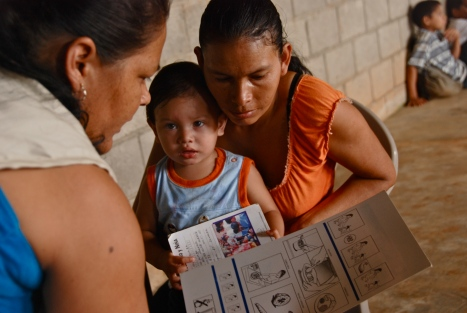A Bolivian Red Cross volunteer teaches a Bolivian woman about child nutrition, part of a program to reduce deaths of children under 5.