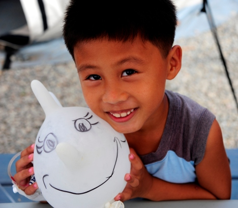 A young boy being treated at the Red Cross field hospital in Ormoc playing with a balloon.